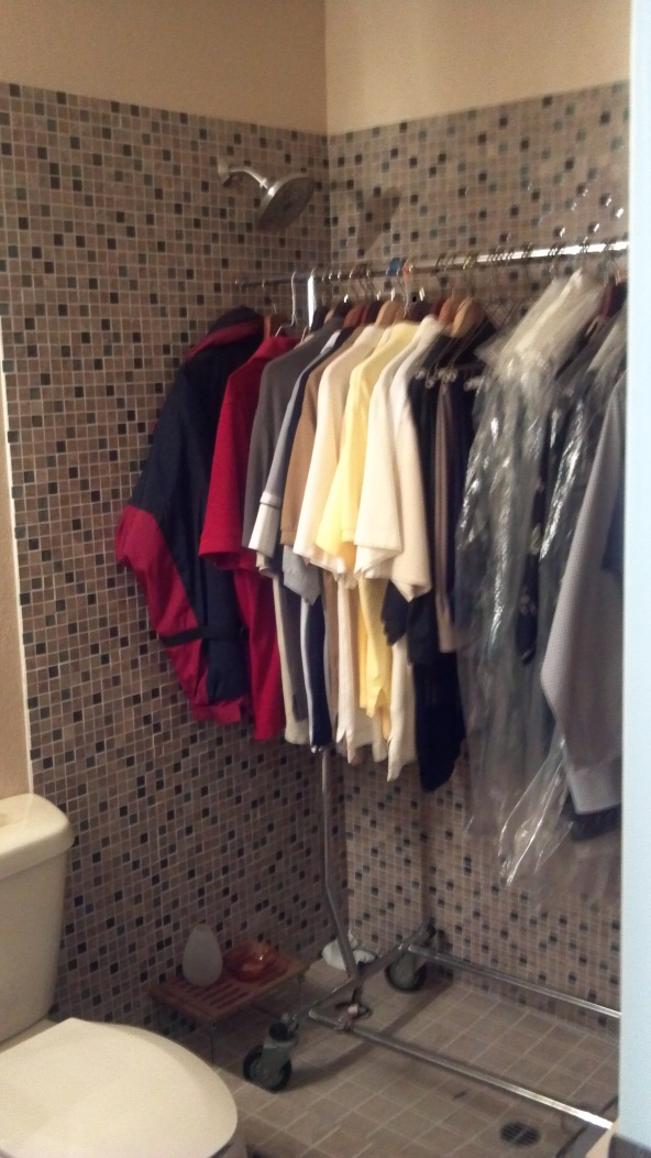 Rick's clothes hanging in our newly tiled guest shower