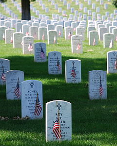 Flags are placed on headstones at Arlington National Cemetery via wikipedia