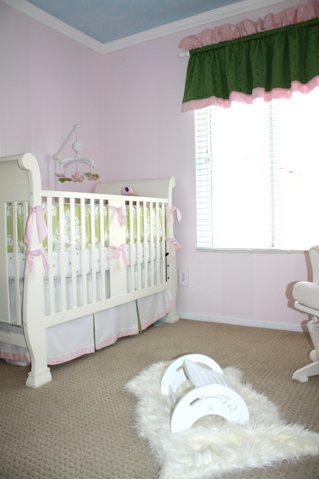 ellas room from floor showing crib, windowtreatments, rocker, rug and paint